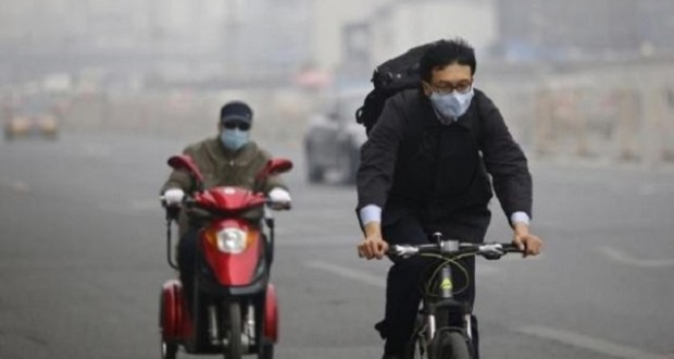Residents wearing masks travel on a bicycle and an electric tricycle along a street on a hazy day in Beijing