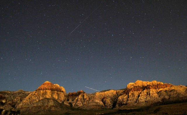 A Perseid meteor and the trail of an jet airplane converge over the cliff walls of Red Rock Canyon near Las Vegas