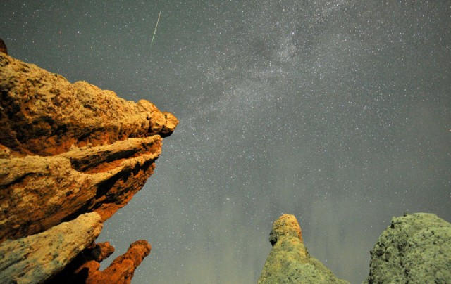 A meteor streaks past stars in the night sky over the village of Kuklici, known for its hundreds of naturally formed stones which resembles human beings, near Kratovo